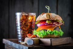 Yummy hamburger with beef, cheese and vegetables. On wooden plank Stock Photos