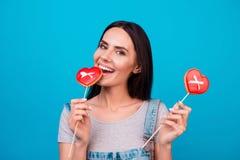 Yummy! Het charmeren jong brunette met rode suikergoedharten op helder stock fotografie