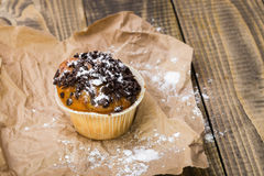 Yummy homemade dessert muffin. With dark chocolate crumb and white sugar powder on brown paper culinary meal on wooden background top view indoor closeup Royalty Free Stock Image