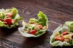 Yummy hoogste meningssamenstelling van verse gezonde salade diende in slabladeren op houten lijst stock foto