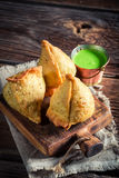 Yummy and hot samosa with green dip. On old table Stock Photos