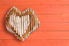 Yummy loaf shaped as heart over orange paneling Royalty Free Stock Photo