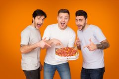 Yummy! Mates Pointing On Pizza Over Orange Background. Yummy! Mates Pointing On Pizza And Looking At Camera Over Orange Background stock photography