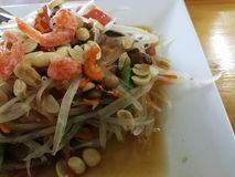 Yummy papaya salad on white plate in Thai restaurant royalty free stock photography