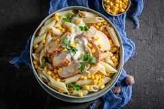 Yummy penne with chicken, corn and bechamel sauce. On black table stock image
