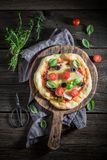 Yummy pizza made of cheese, tomatoes and herbs. On old wooden table Stock Photography