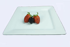 Yummy. An raspberry and two strawberries on a white plate with a white back ground Royalty Free Stock Photo