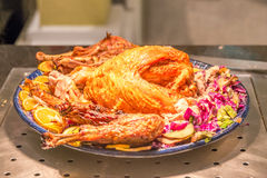 Yummy roast turkey with vegetables and fruits under yellow spotlight. Stock Photo
