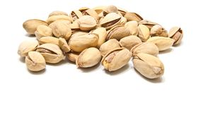 Yummy roasted pistachios closeup. Heap of yummy pistachios closeup on white royalty free stock images