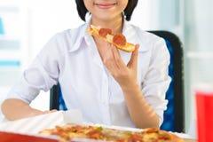 Yummy slice. Happy businesswoman having a yummy slice of pizza Stock Image