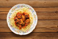 Yummy spaghetti with meatballs in tomato sauce on wooden table Royalty Free Stock Photo
