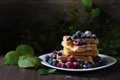 Yummy sweet waffles with raspberries and blueberries  . Yummy sweet waffles with raspberries and blueberries on a old wooden table Royalty Free Stock Photos