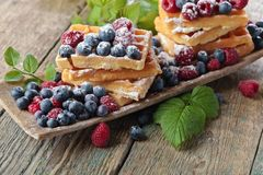 Yummy sweet waffles with raspberries and blueberries on a woode. Yummy sweet waffles with raspberries and blueberries on a old wooden table Stock Photography
