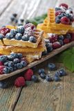 Yummy sweet waffles with raspberries and blueberries . Yummy sweet waffles with raspberries and blueberries on a old wooden table Stock Photography