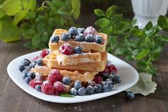 Yummy sweet waffles with raspberries and blueberries. Yummy sweet waffles with raspberries and blueberries on a old wooden table Royalty Free Stock Image
