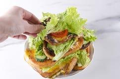 Yummy vegetarische toosts Vrouwenhand die één of andere sandwich met verse groenten nemen stock foto's
