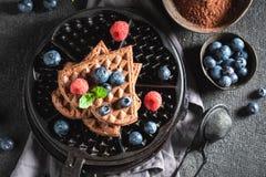 Yummy wafels van cacao met verse bessen worden gemaakt die stock foto's