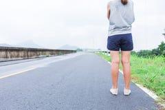Yung站立在街道上的妇女腿和鞋子 免版税库存图片