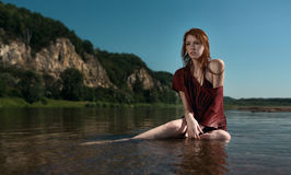 Yung beautiful redhead girl in the burgundy shirt sitting in the river. Yung beautiful redhead girl in wet burgundy shirt sitting in the river on a background of Stock Photography