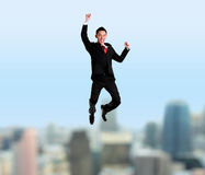 Yung businessman jumping with cityscape on the background Royalty Free Stock Image