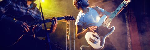 Male guitarists performing at nightclub. Yung male guitarists performing ono stage at nightclub Royalty Free Stock Photos