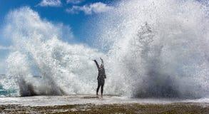 Yung woman enjoying the moment when huge Powerful Waves crashing on rocks stock photos