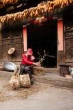 """Yunnan, Porcelanowy †""""MARZEC 2, 2012: Chiński stary człowiek robi kukurydzanego krzesła przed starym powabnym chińczyka domem,  obrazy royalty free"""