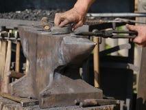 Yunque de acero, encima del cual miente un objeto caliente que es sostenido por un par de alicates El herrero sostiene los alicat fotografía de archivo libre de regalías