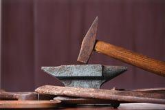 Yunque rugoso oxidado viejo, martillo y otras herramientas del herrero Imagen de archivo