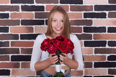 Yuong beautiful blond girl with bouquet of roses Stock Photos