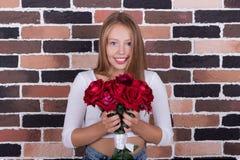 Yuong härlig blond flicka med buketten av rosor Arkivfoton