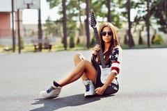 Yuong kvinna med gitarren utomhus- kvinna för stil för blåtiraframsidamode sexig Arkivfoton