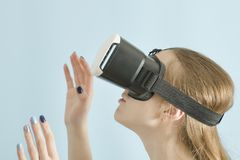 Yuong woman with glasses of virtual reality. Blue background Royalty Free Stock Photography