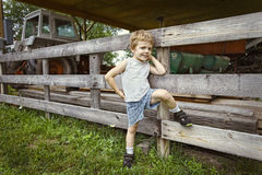 Yup, that's my tractor!. Young boy posing on fence at farm Royalty Free Stock Photo