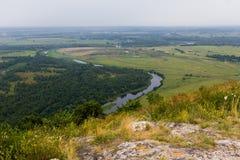 Yuraktau视图从山到领域,河,森林 库存照片
