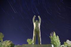 Yuri Gagarin monument. Baikonur. Startrails background. Yuri Gagarin monument. Bottom view. Baikonur. Startrails and trees background. The stars are moving in a stock photos