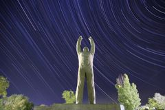 Yuri Gagarin monument. Baikonur. Startrails background. Yuri Gagarin monument. Bottom view. Baikonur. Startrails and trees background. The stars are moving in a royalty free stock photos