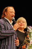 Yuriy Galtsev在她的诞生的那天祝贺斯韦特兰娜Kryuchkova,发音庄严的讲话并且给花 免版税库存图片