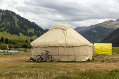 Yurt in Central Asian Veld. Traditional Mongol Nomad Housing assembled on Green Meadow among High Mountain Hills in Kyrgyzstan and a Bicycle lean on it Royalty Free Stock Photo
