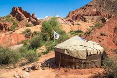Yurt with flag. Traditional hous of Nomad people of Kyrgys republic  in red rocks on south of Issyk-Kul lake on the east of Kyrgyzstan Kyrgyz republic. famous Stock Photo