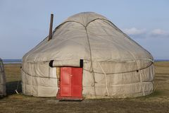 Yurt with red door at Song Kul lake in Kyrgyzstan. Asia Stock Image