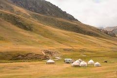 Yurts asiáticos de los nómadas en el prado hermoso de la montaña en Kirguistán fotografía de archivo libre de regalías