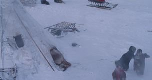 Yurts camp in the middle of Arctic children happy playing outside wearing a traditional fur clothes. 4k stock video footage