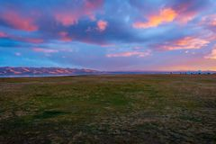 Sunset over the hills around Song Kul lake. Yurts and mountains around Song Kul lake in a sunset light, Kyrgyzstan Stock Images