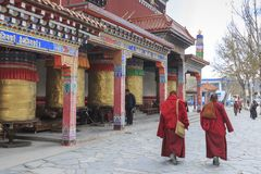 Tibetan people and monks walking around the Mani Temple Mani Shicheng a famous landmark in the Tibetan city of Yushu Jyekundo, Qin Royalty Free Stock Image