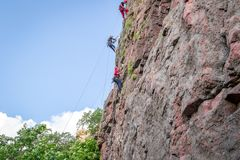 Yuzhnoukrainsk,乌克兰- 2018年6月19日:攀岩 一个小组年轻攀岩运动员攀登垂直的花岗岩岩石 库存图片