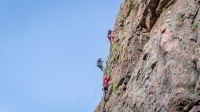 Yuzhnoukrainsk,乌克兰- 2018年6月19日:攀岩 一个小组年轻攀岩运动员攀登垂直的花岗岩岩石 库存照片