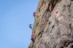 Yuzhnoukrainsk,乌克兰- 2018年6月19日:攀岩 一个小组年轻攀岩运动员攀登垂直的花岗岩岩石 免版税库存照片