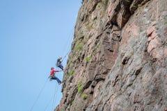 Yuzhnoukrainsk,乌克兰- 2018年6月19日:攀岩 一个小组年轻攀岩运动员攀登垂直的花岗岩岩石 免版税图库摄影
