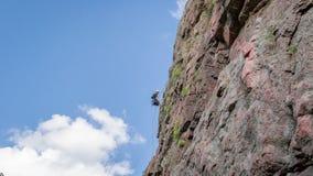 Yuzhnoukrainsk,乌克兰- 2018年6月19日:攀岩 一个年轻登山人攀登一个垂直的花岗岩岩石 极其体育运动 免版税库存照片